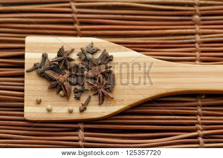 Star Anise or bunga lawang on wooden spatula with textured background