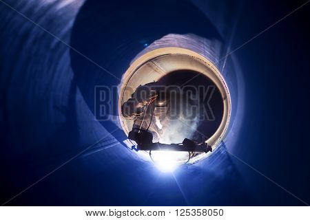 A worker engaged in the pipe welding on the pipeline construction