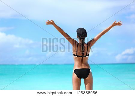 Happy freedom bikini woman on free tropical beach summer vacation. Joyful girl from behind with arms raised up in success swimming in ocean water sunbathing happily. Winning and carefree.