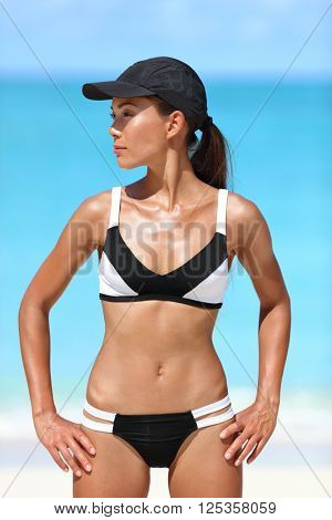 Sporty bikini fitness woman sun tanning sexy body on summer beach vacations. Active healthy Asian girl model standing in watersports swimwear against ocean background on sunny travel vacation.