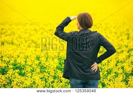 Woman agronomist standing in the field of blooming cultivated rapeseed plantation female agricultural expert looking to distant point on the horizon over oilseed rape landscape.