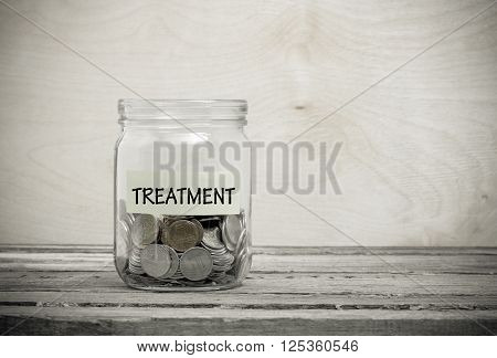 Label on a glass jar with the inscription - treatment. Glass jar with coins. Financial concept on wooden background