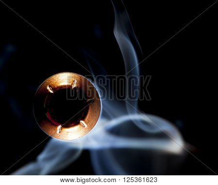 Copper colored hollow point bullet with smoke on a dark background