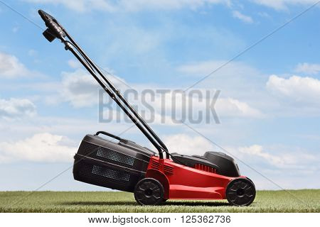 Lawn mower on a green grass and blue sky background