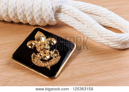 Orderliness White Scout Rope With Vintage Boy Scouts Badge On Wooden Table.