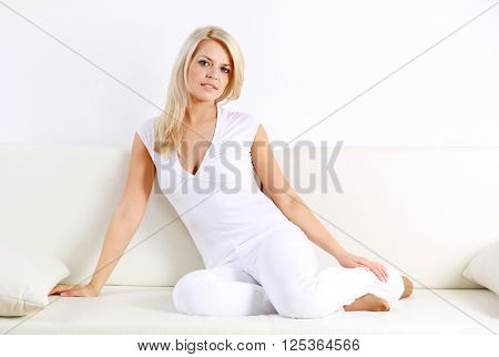 Portrait of attractive mature woman sitting at sofa and relaxing at home.