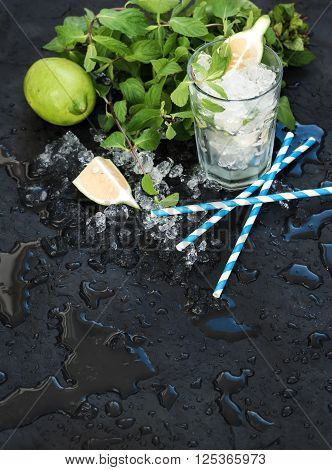 Mojito cooking set. Bunch of fresh mint, lime, chipped ice and coctail glass over black slate stone backdrop, selective focus, copy space