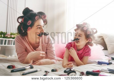 Funny family! Mother and her child daughter girl with a paper accessories. Mother and daughter preparing for a party and having fun. Beautiful young woman and funny girl with a paper mustache on stick