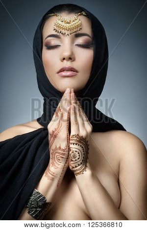 Beautiful fashion east woman portrait.Asian girl in a black headscarf praying. East girl with henna tattoos.Hindu model with perfect make-up.India.Asia
