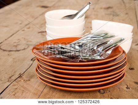 Dish dark brown many dishes stacked fork Cup white stackable on wooden table.