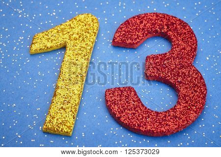 Number thirteen yellow red color over blue background. Anniversary. Horizontal