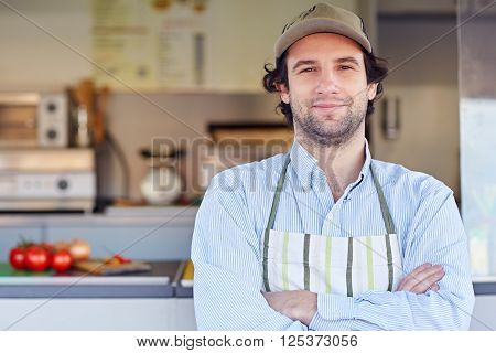 Proud small business owner standing in front of his business where he makes and sells takeaway food