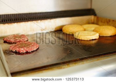 Two burger patties frying next to each other with open buns being toasted nearby ** Note: Shallow depth of field