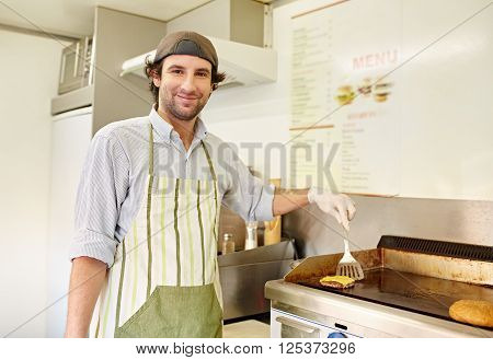 Smiling male fry cook looking pleased while frying a freshly made hamburger patty in a takeaway food stall kitchen