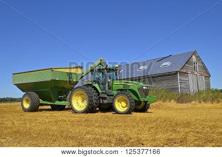 MAYVILLE, NORTH DAKOTA-August 19, 2015: A tractor and grain cart cart in a  wheat harvest scene are products of John Deere Co, an American corporation that manufactures agricultural, construction, forestry machinery, diesel engines, and drivetrains.