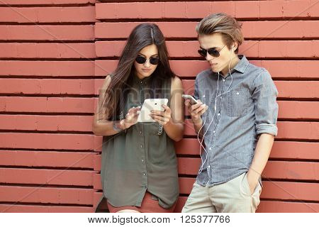 Young people having fun outdoor using gadget like a smartphone and pad against red wall. Urban lifestyle, internet and gadget dependence, friends, social network concept. Image toned and noise added.