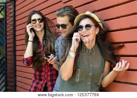 Young girls and boy having fun outdoor and using smart phone against red brick wall. Urban lifestyle, happiness, joy, friends, social network concept. Image toned and noise added.