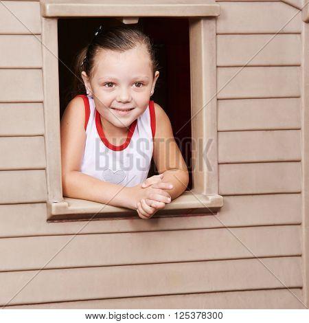 Happy girl looking through the window of a playhouse in kindergarten