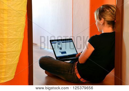 Bytca Slovakia - April 27 2012: Young woman browses her facebook page on laptop seated on the floor