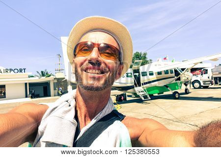 Cheerful man selfie at airport with airplane background - Passenger tourist taking self photo after plane landed at Panay island - Concept of joyful world travel and alternative air transport trip