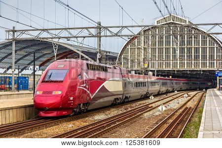 Amsterdam, Netherlands - June 9, 2014: TGV Thalys high-speed train at Amsterdam Centraal railway station. Thalys trains connect Paris, Brussels, Amsterdam and Cologne