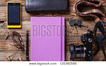 Overhead view of travel gear placed on wooden table. Mobile phone, earplugs, violet sketchbook, pencil, camera and purse. Flat lay top view.