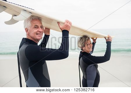 Portrait of senior couple in wetsuit carrying surfboard over head on the beach