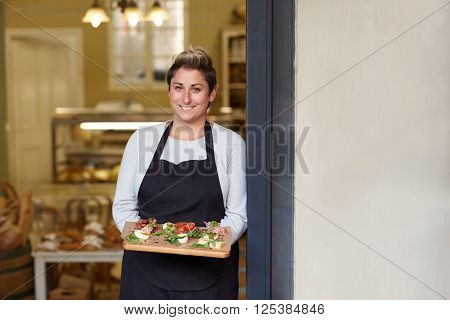 A young female deli employee standing in the doorway