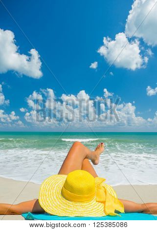 young beautiful woman with hat  relaxing on sand beach