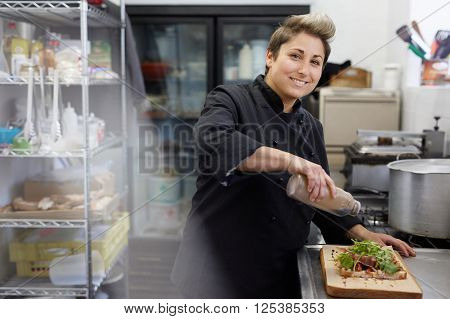 A female chef drizzling balsamic vinegar on an open sandwich ** Note: Soft Focus at 100%, best at smaller sizes