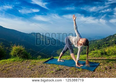 Woman doing Ashtanga Vinyasa yoga asana Parivrtta trikonasana - revolved triangle pose outdoors in mountains in the morning