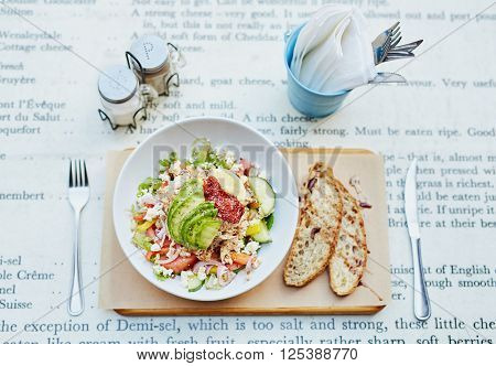 Overhead view of a simple place setting at an eatery consiting of a fresh salad with fresh bread, cutlery, condiments and serviettes
