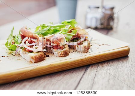 Gourmet meal of bruschetta topped with toamto, onion, parma ham and rocket, presented on a wooden board with condiments in the background poster
