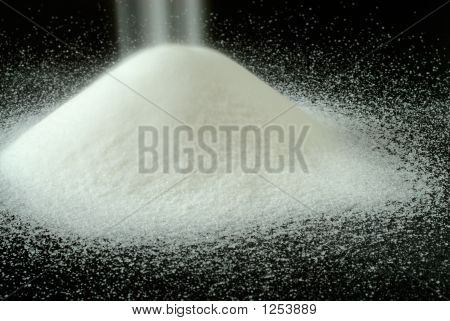 Sugar Falls On A Mountain Of Granulated Sugar On A Black Backgro