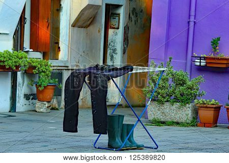 Fisherman's Pants And Boots Dry In A Courtyard Of The Apartment Near The Sea Port