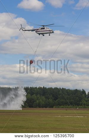 Minsk Belarus-June 21 2014: Staff of Ministry of Emergency Situations Spraying Water over Trees on MI-8 Helicopter During Aviation Sport Event Dedicated to the 80th Anniversary of DOSAAF Foundation in Minsk on June 21 2014 in Minsk Belarus