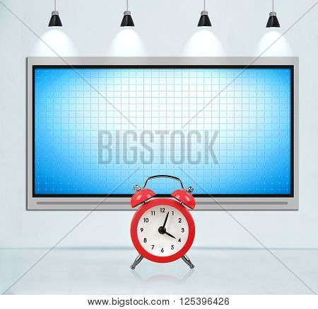 Blank tv screen on concrete wall in loft room. Big red clock. Deadline concept.