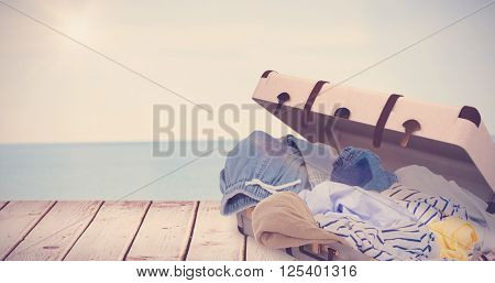 Composite image of unfolded clothes against water edge at the beach