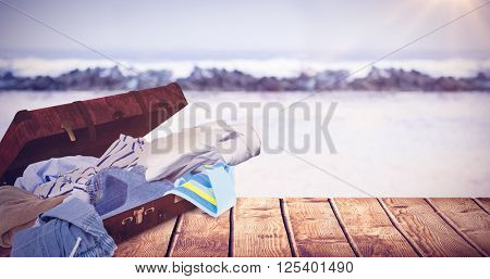 Composite image of unfolded clothes against view of waves