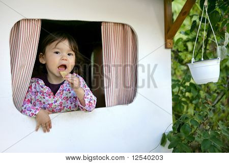 Portrait of a little girl eating a biscuit