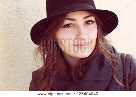 portrait of a girl with green eyes and foxy hair in a black hat and scarf standing near light wall and looking at the camera