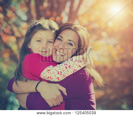 Beautiful mother and daughter hugging against fall background with instagram style filter