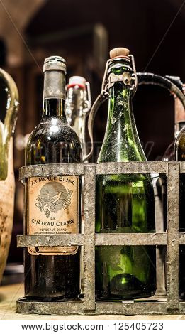 Bordeaux, France - March 24, 2016. Antiques french wine bottles from Bordeaux in a vintage metal bottle carrier. Aquitaine, France.