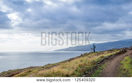 Woman traveler with backpack is watching at the map of hiking path. East coast of Madeira island scenics, Portugal.