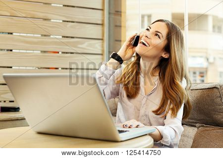 Young woman on the phone in a cafe with a laptop on the table