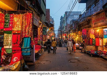 DELHI, INDIA - JANUARY 2, 2010: People in Chitli Qabar Bazar market street of Old Delhi in the evening