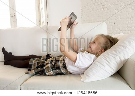 young sweet cute and beautiful 6 or 7 years old girl with blond hair in school uniform lying on home sofa couch using internet app on digital tablet pad playing online game smiling happy