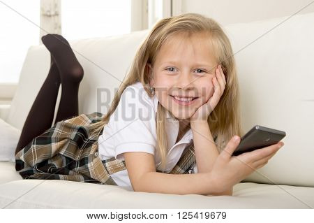 sweet cute and beautiful 6 or 7 years blond old little girl in school uniform lying on home sofa couch using internet app on mobile phone playing online game looking happy and relaxed