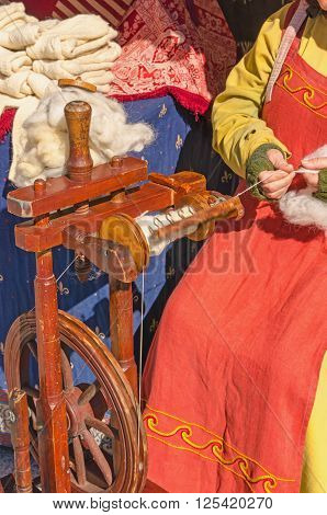 Woman Working On Old Spinning Wheel