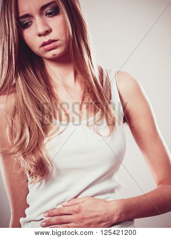 Bellyache indigestion or menstruation. Young woman suffering from stomach pain studio shot on gray